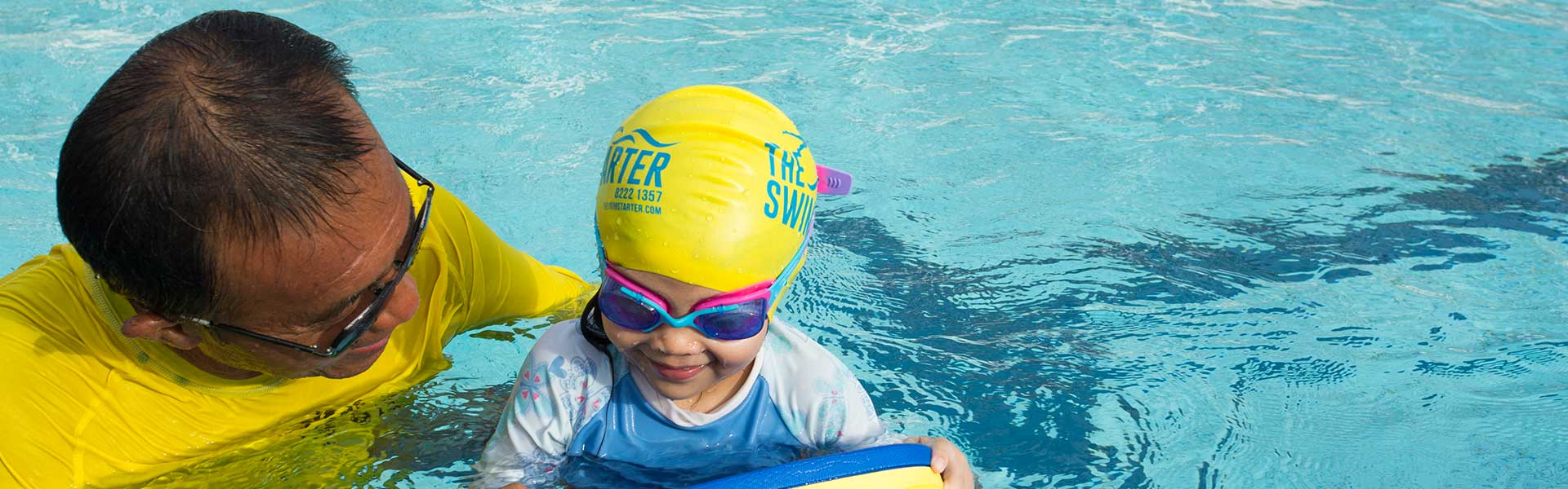 Young child Swimming in deep pool with coach and board balancing